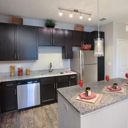 Apartment kitchen with island and pendant lighting and hardwood floors | Village at Terra Bella rentals