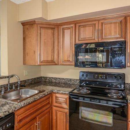 Kitchen with granite countertops and black appliances with over the range microwave | Windward at the Villages