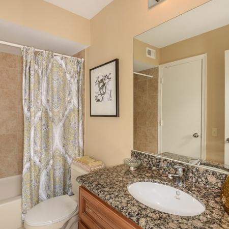 Bathroom with granite countertops, shower with tile walls