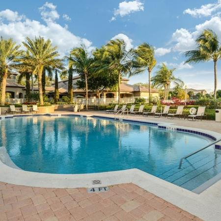 Apartment community pool with poolside lounge chairs