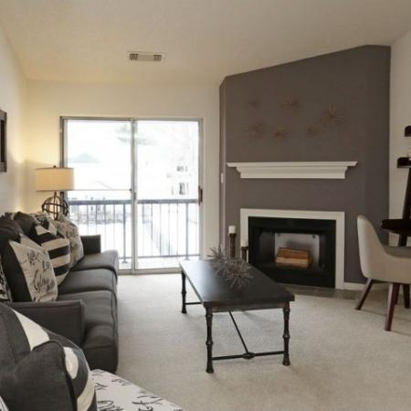 Apartment living room with carpeted flooring, fireplace, and doors to private balcony | The Pavilions