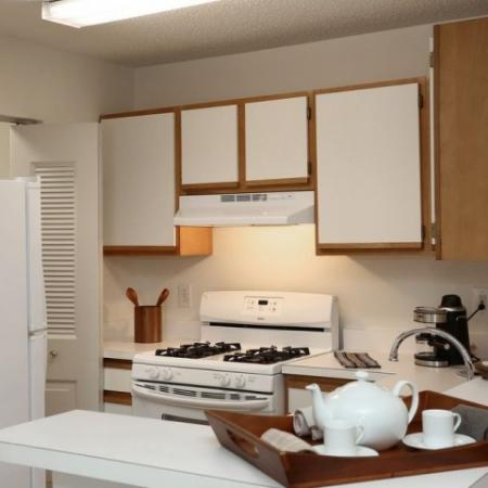 Kitchen with white cabinets and white appliances at The Pavilions apartments