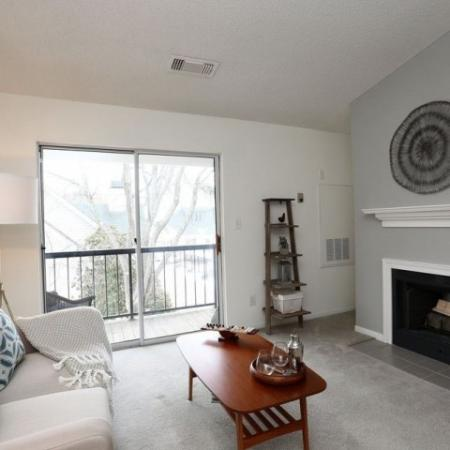 2 bedroom apartment living room with fireplace and doors to private balcony