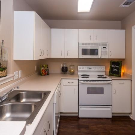 Apartment kitchen with white cabinets and white appliances | River Stone Ranch | Austin