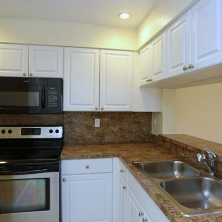 Kitchen with spacious granite style counters, stainless steel sinks, and classic white cabinets | Jupiter Isle