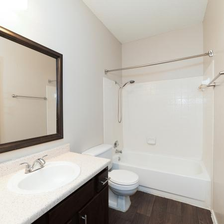 Renovated apartment bathroom with white counter, dark cabinets