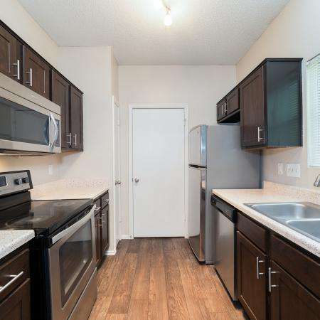 Renovated kitchen with dark cabinets, black appliances and wood flooring