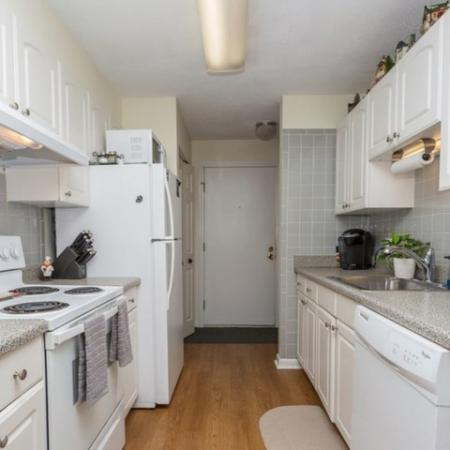 Apartment kitchen with white cabinets, white appliances and hardwood floors | Tatnuck Arms in Worcester