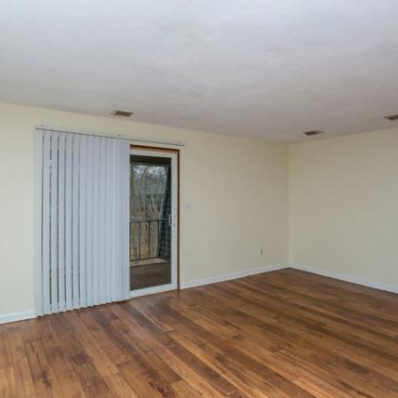Apartment living room with hardwood floor and sliding glass door to the balcony in Tatnuck Arms apartment complex