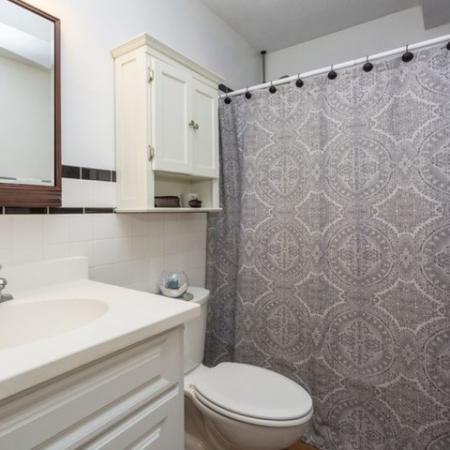 Bathroom with white cabinets and tiled walls | Tatnuck Arms