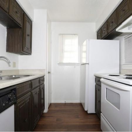 Apartment kitchen with dark cabinets and white appliances | Royal Crest