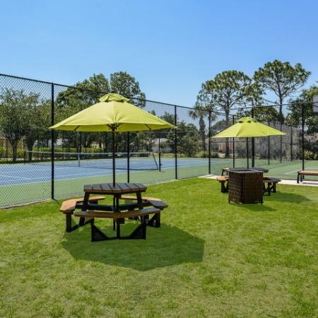 Picnic tables by community tennis and basketball courts | Lakeside at Greenboro
