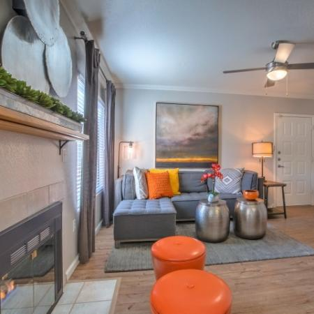 Apartment living room with wood floors, fireplace, and ceiling fan | Altezza rentals in Albuquerque