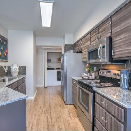 Apartment kitchen with hardwood floors, stainless steel appliances with microwave, modern custom cabinets, tile backsplash | Altezza apartments NM