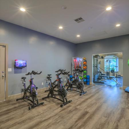 spin bike room with bikes, stretching equipment and fitness ondemand tv | Altezza apartments