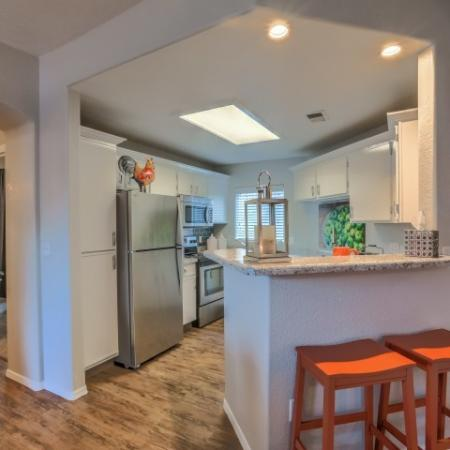 Kitchen with white cabinets and stainless steel appliances and breakfast bar | Albuquerque apartment homes