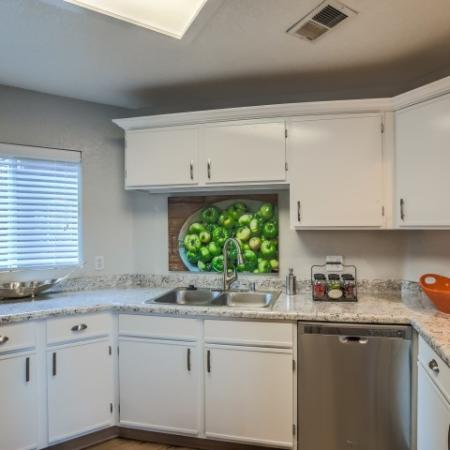 Kitchen with white cabinets, two basin sink and stainless steel dishwasher