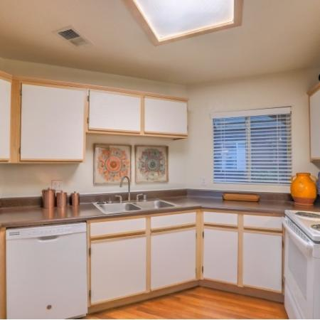 Kitchen with wood floors, white wood cabinets, white appliances and double basin sink