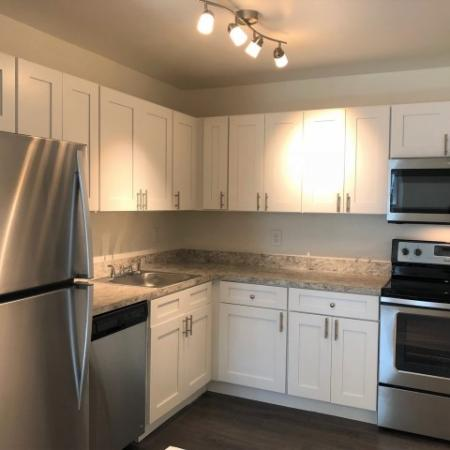 Renovated kitchen | Brittany apartments | white cabinets, stainless steel appliances including microwave