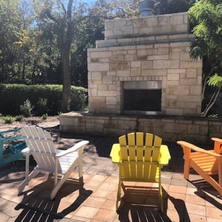 Outdoor fireplace with adirondack chairs | Austin apartment community