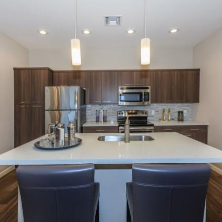 Open kitchen with dark cabinets, light countertops, stainless steel appliances.