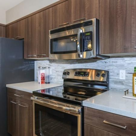 Kitchen features stainless appliances, built-in microwave, tile backsplash and white countertops