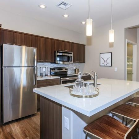 Modern kitchen with dark light countertops, tile backsplash and island | The Canyons at Linda Vista Trail apartment homes