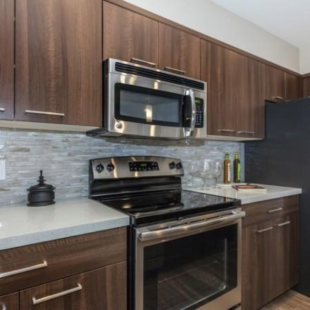 Kitchen with high end finishes | Stainless steel appliances, light countertops, wood cabinets, hardwood floors