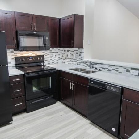modern kitchen with granite countertops, black appliances, tile backsplash | Gateway Club
