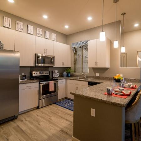 Kitchen with stainless steel appliances and hardwood flooring | apartments in Pima Canyon
