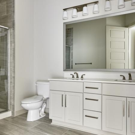 Bathroom with large mirror, light cabinets and hardwood flooring