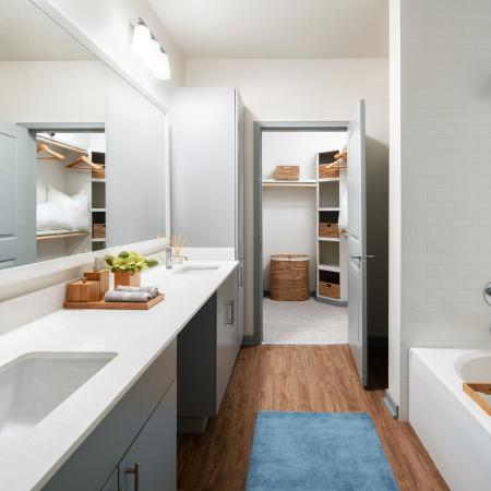 Bathroom with dual vanity, hardwood style floors | The District apartments