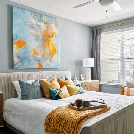 Bedroom with ceiling fan and large windows | The District at Rosemary | Sarasota