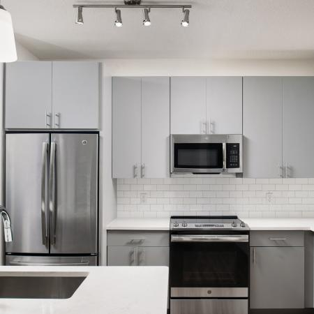kitchen with quartz countertops, stainless appliances | gooseneck sink | Rosemary district apartments