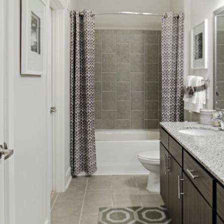 1 bedroom apartment | bathroom with wood cabinets, hardwood floors