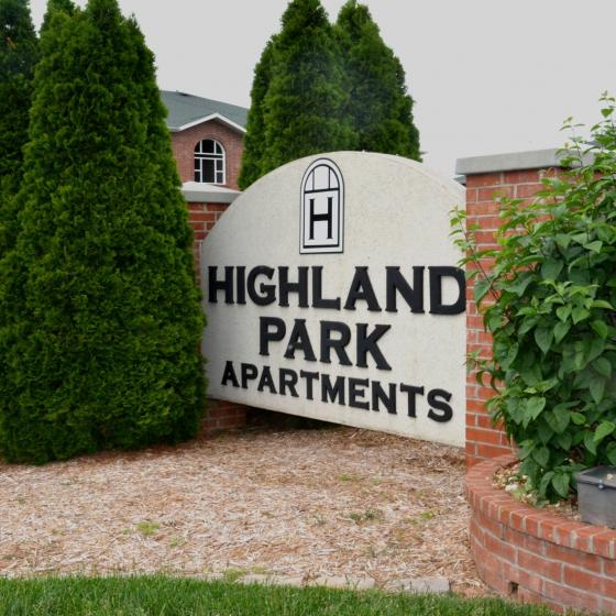 Highland Park Apartments monument sign in front of the exterior apartment building