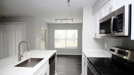 White Quartz Counters and Stainless Appliances in Kitchen | Alister Town Center Columbia