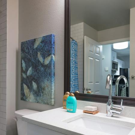 Redesigned Bathrooms with Granite Counters and Tile Surrounds