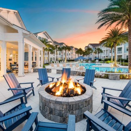 poolside lit fire pit with apartment buildings at dusk