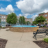 fountain and bench with apartment buildings on sunny day